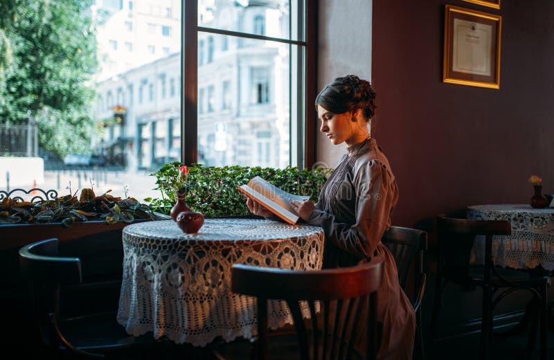 Retrato da senhora no livro de leitura do café perto da janela foto de stock