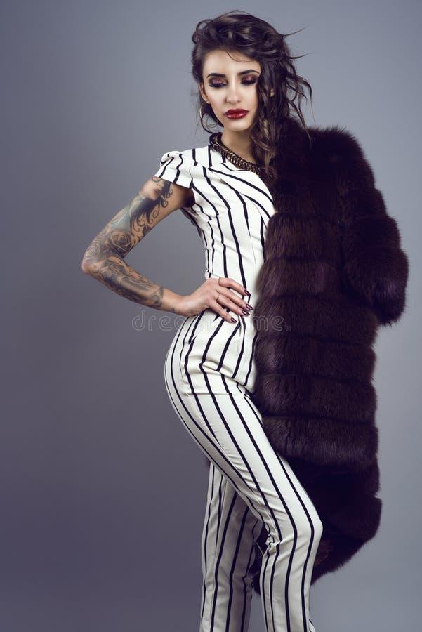 Retrato da senhora tattooed de cabelo escuro chique nova que veste o macacão listrado à moda com luvas curtos e a colar esplêndid imagem de stock