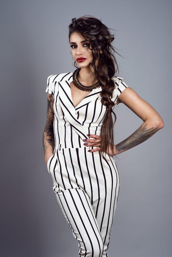 Retrato da senhora tattooed de cabelo escuro lindo nova com a trança que veste o macacão listrado à moda com luvas curtos e colar imagens de stock royalty free