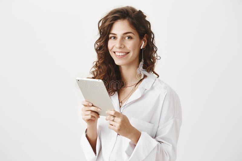 Retrato da tabuleta guardando fêmea caucasiano positiva e bem sucedida, música de escuta nos earbuds sem fio, sorrindo fotos de stock