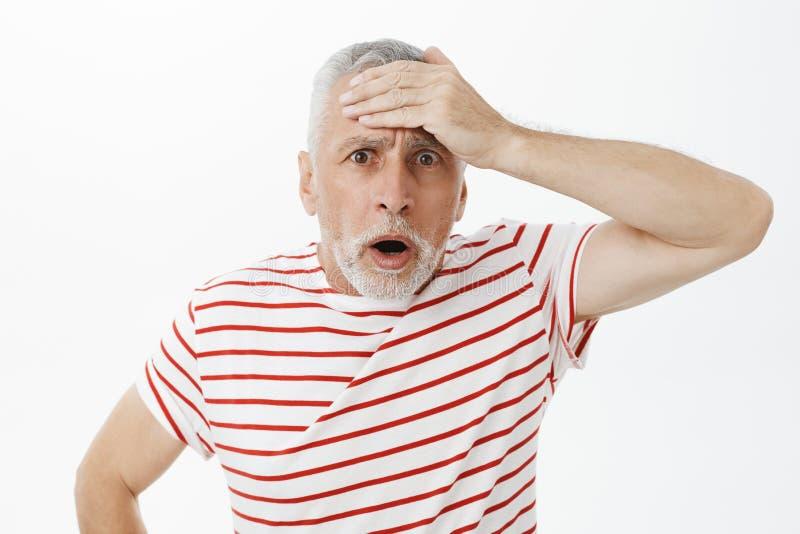 Retrato da testa de perfuração chocada do ancião interessado sem-palavras com a palma com a boca aberta incomodada e a vista do o fotos de stock royalty free