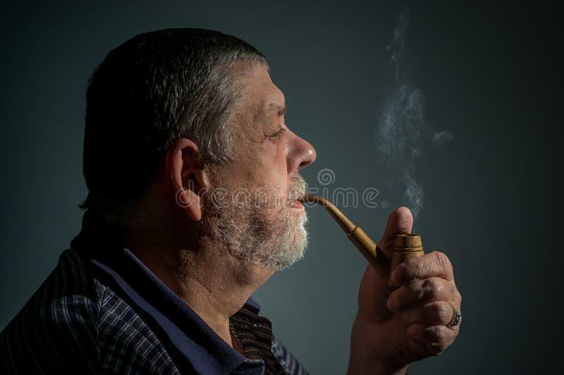 Retrato da tubulação de cigarro de fumo do homem farpado caucasiano contra o fundo escuro foto de stock