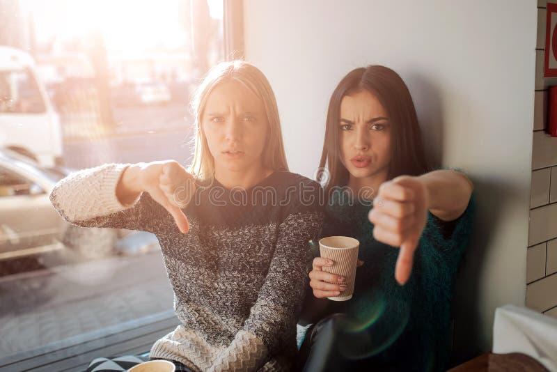 Retrato da vista dianteira de dois amigos engraçados com polegares para baixo e olhando à câmera imagens de stock