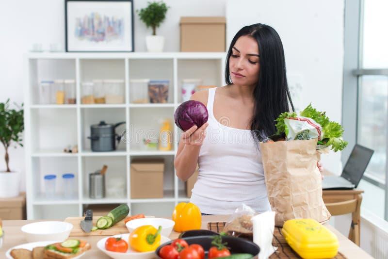 Retrato da vista dianteira de uma dona de casa que olha com cuidado e que guarda a couve, escolhendo o bom ingrediente fresco par imagens de stock royalty free
