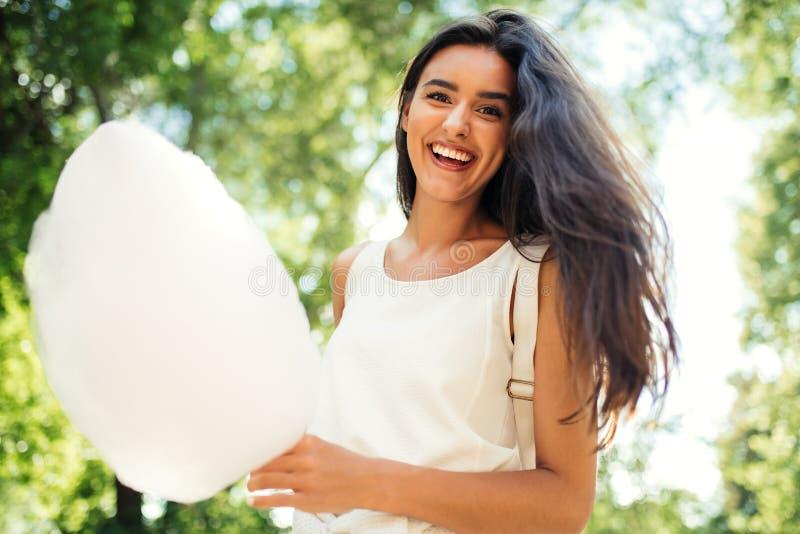 Retrato da vista inferior do sorriso bonito e feliz da jovem mulher com o algodão doce na natureza fotografia de stock royalty free
