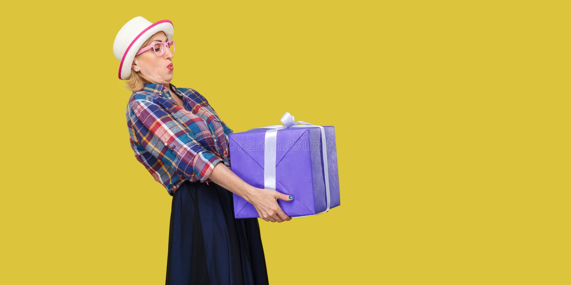Retrato da vista lateral da avó moderna querendo saber alegre no chapéu branco e na posição quadriculado da camisa e na tentativa fotografia de stock