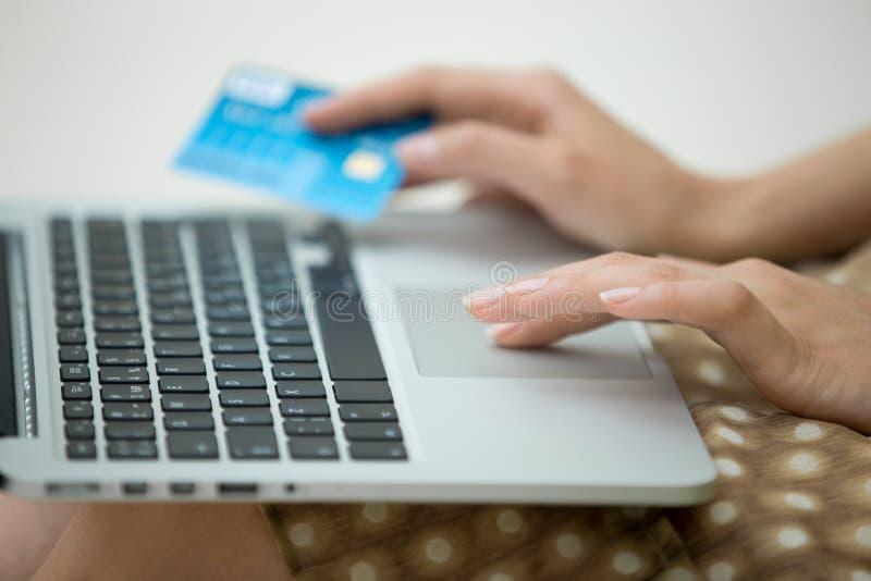 Retrato da vista lateral da mulher com cartão de crédito usando o portátil fotografia de stock