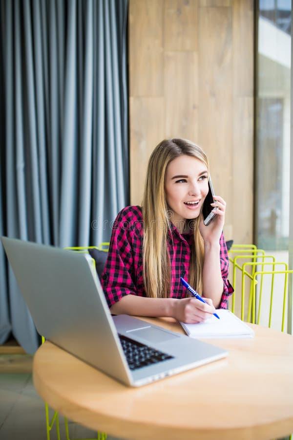 Retrato da vista lateral da mulher de negócios nova que tem a chamada do negócio no escritório, seu local de trabalho, redigindo  imagem de stock royalty free