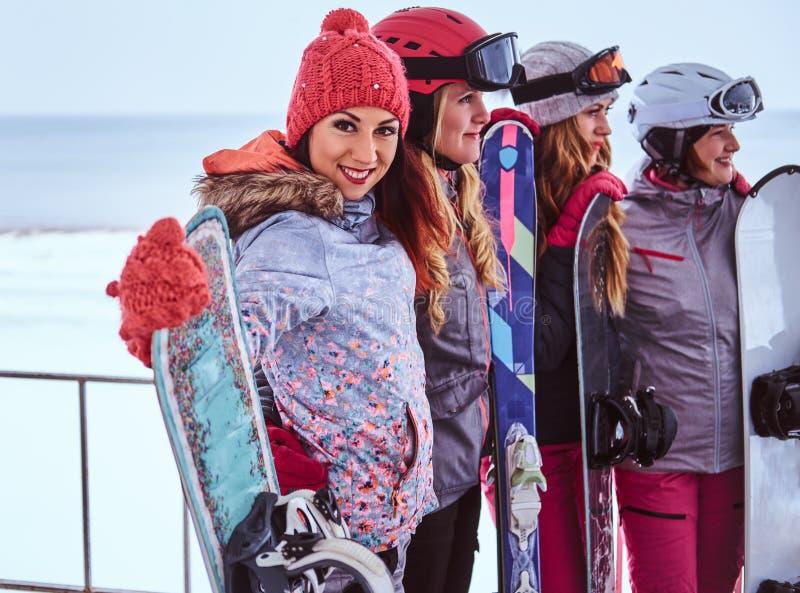Retrato da vista lateral de amigos das mulheres na roupa do inverno dos esportes que guarda snowboards foto de stock