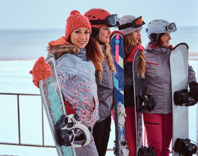 Retrato da vista lateral de amigos das mulheres na roupa do inverno dos esportes que guarda snowboards imagens de stock royalty free
