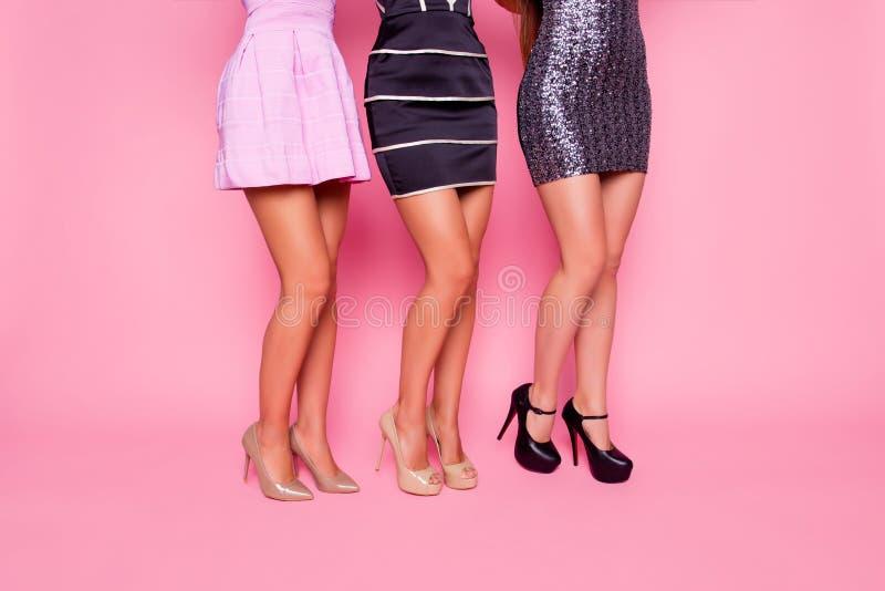 Retrato da vista lateral de três meninas bonitas no vestido que mostra seus pés lisos no fundo cor-de-rosa fotografia de stock royalty free