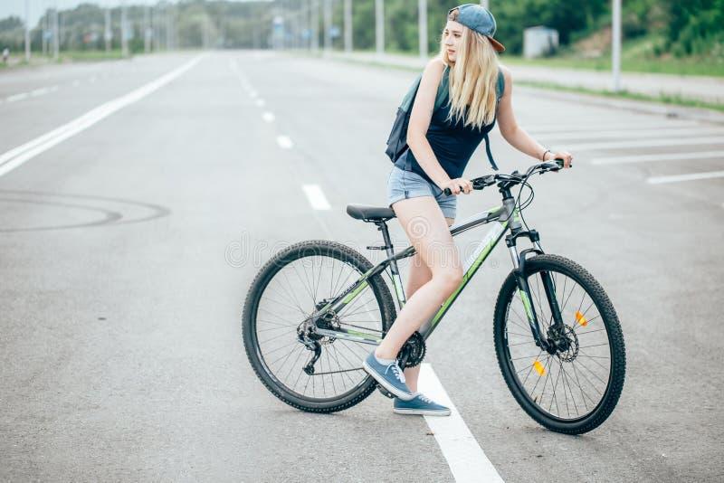 Retrato da vista lateral de uma equitação bonita nova da mulher na bicicleta na rua da cidade foto de stock royalty free