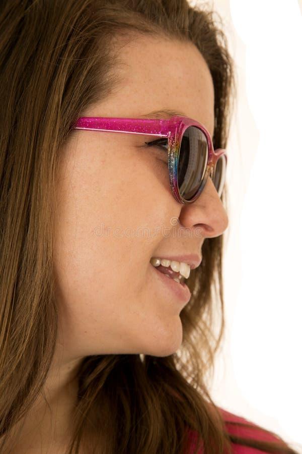 Retrato da vista lateral de uma jovem mulher que veste óculos de sol cor-de-rosa fotos de stock