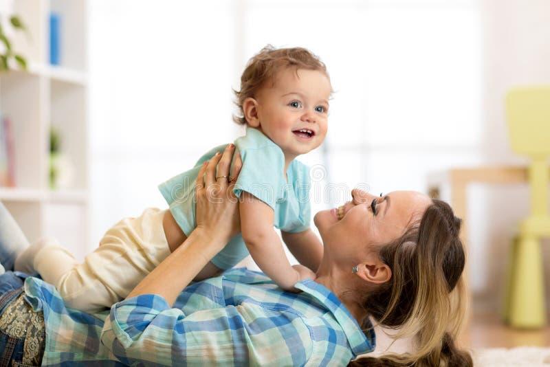 Retrato da vista lateral de uma mãe feliz que encontra-se no assoalho com seu filho do bebê fotos de stock