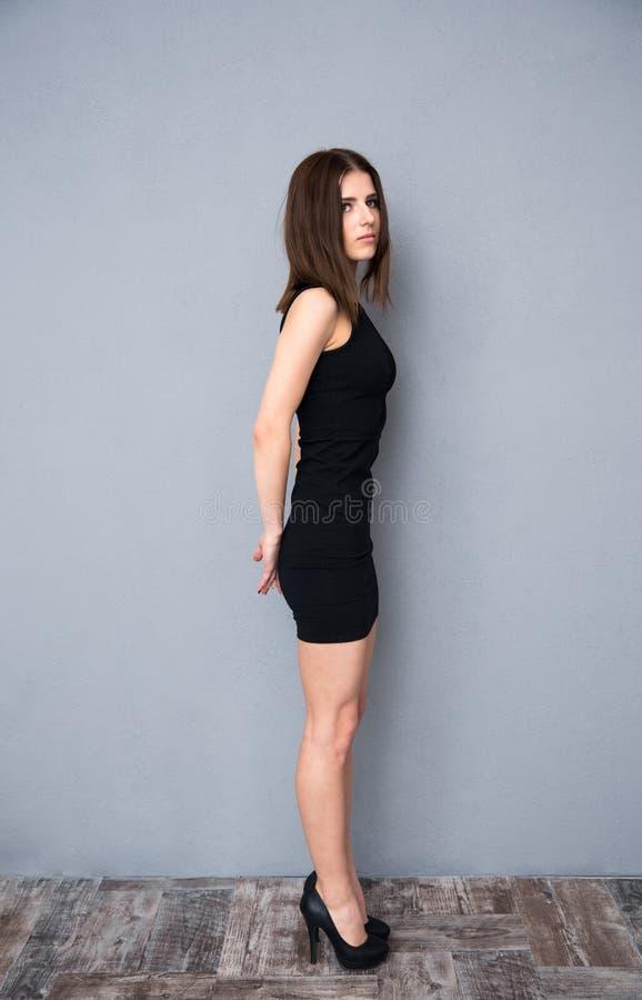 Retrato da vista lateral de uma mulher bonito no vestido preto foto de stock