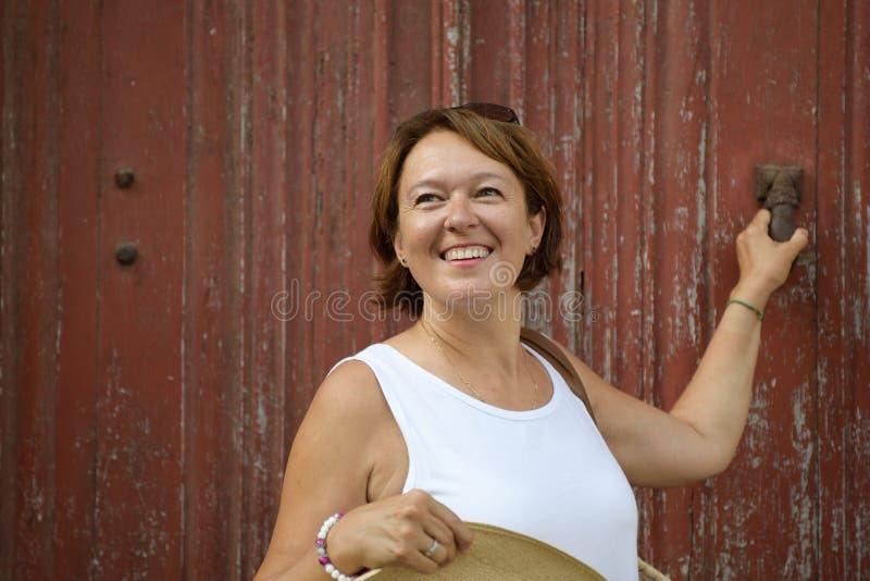 Retrato da vista lateral de uma mulher que sorri no fundo vermelho imagem de stock royalty free