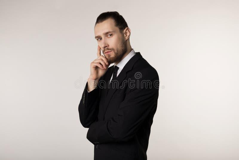 Retrato da vista lateral do homem de negócios novo atrativo no terno preto com mão à moda da terra arrendada do penteado no queix imagens de stock