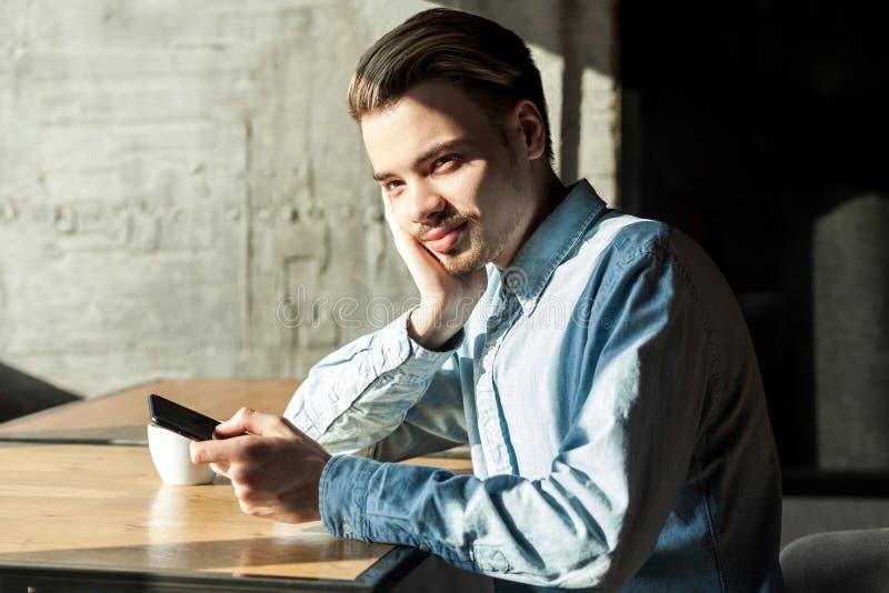 Retrato da vista lateral do homem farpado novo atento satisfeito na camisa azul da sarja de Nimes que senta-se no café e que guar foto de stock