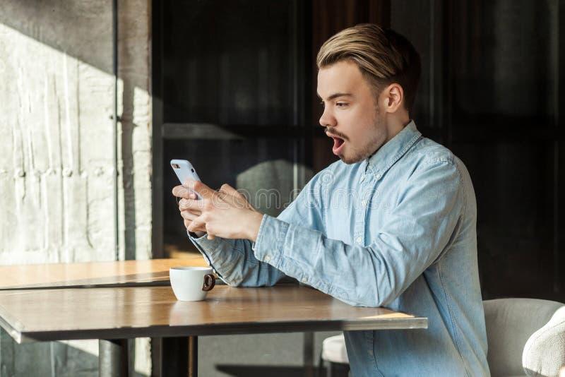Retrato da vista lateral do homem novo chocado na camisa azul da sarja de Nimes que senta-se no café e que lê a notícia inacredit imagem de stock