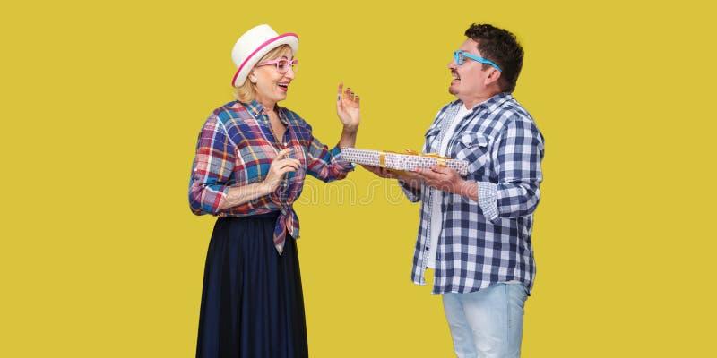 Retrato da vista lateral dos pares de amigos felizes, homem e mulher na posição quadriculado ocasional da camisa e marido que dá  imagens de stock