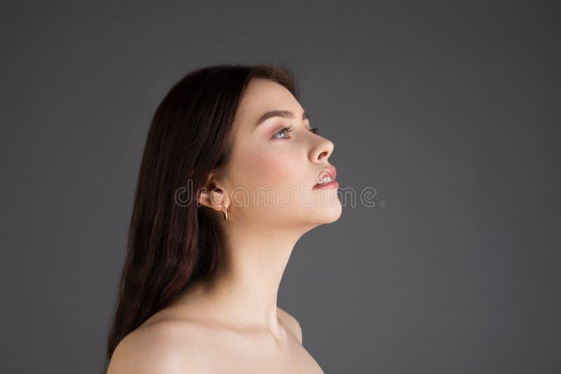 Retrato da vista lateral da fêmea nova atrativa com cabelo moreno fotos de stock