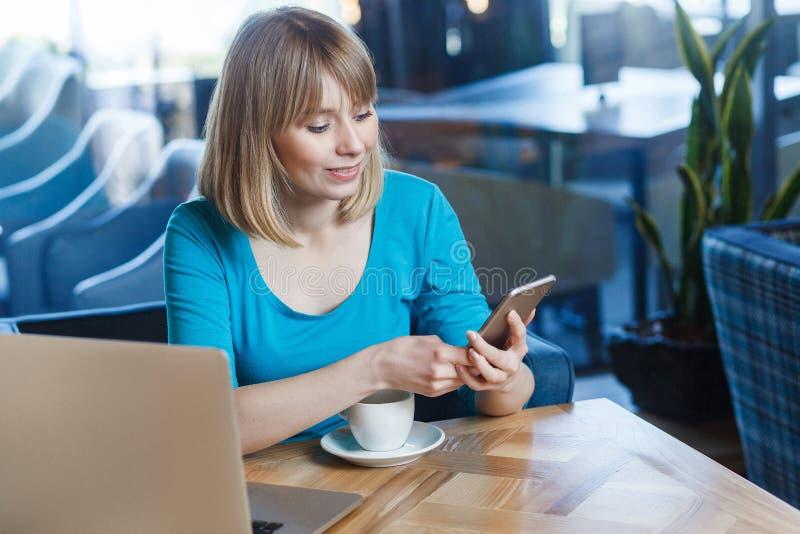 Retrato da vista superior da mulher loura feliz nova no t-shirt azul, sentando-se no café e guardando seus telefone e texting esp imagem de stock