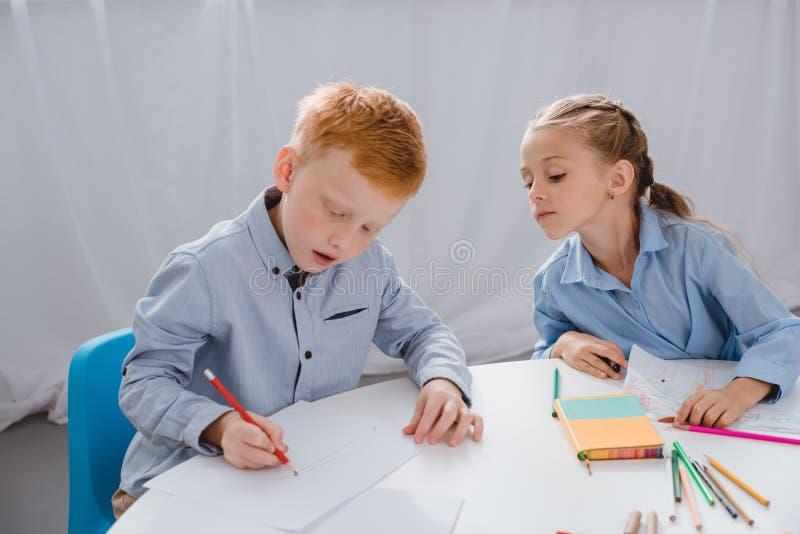 retrato das crianças adoráveis que tiram imagens na tabela imagens de stock