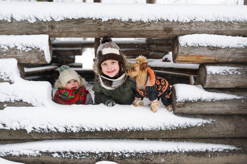 Retrato das crianças e do cão pequeno na perspectiva da casa coberto de neve inacabado na vila fotos de stock royalty free