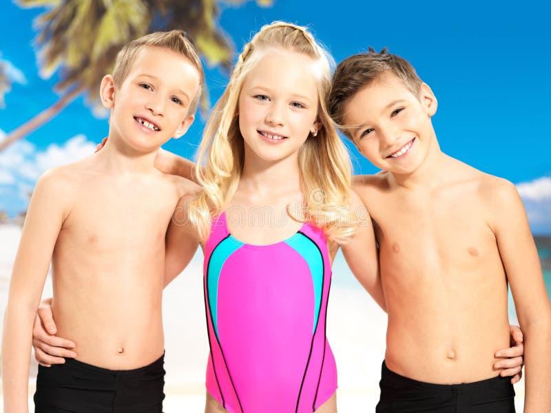 Retrato das crianças felizes que apreciam na praia fotos de stock