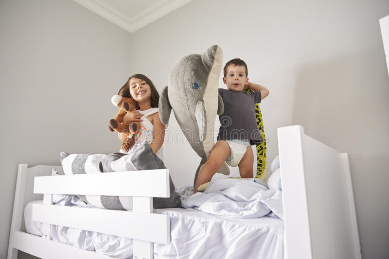 Retrato das crianças que jogam com os brinquedos na cama de beliche imagens de stock