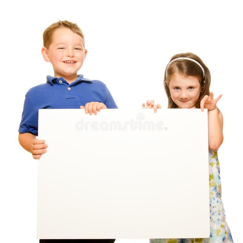 Retrato das crianças que prendem o sinal em branco imagem de stock royalty free
