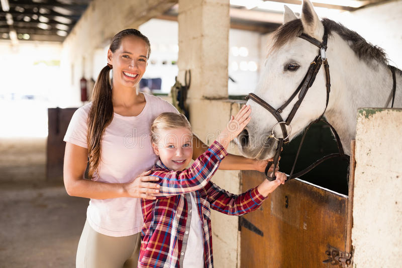 Retrato das irmãs que afagam o cavalo fotografia de stock