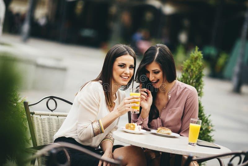 Retrato das jovens mulheres bonitas que comem o bolo imagens de stock royalty free