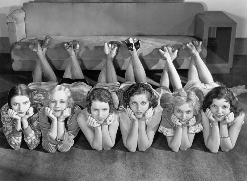 Retrato das jovens mulheres na fileira no assoalho fotografia de stock