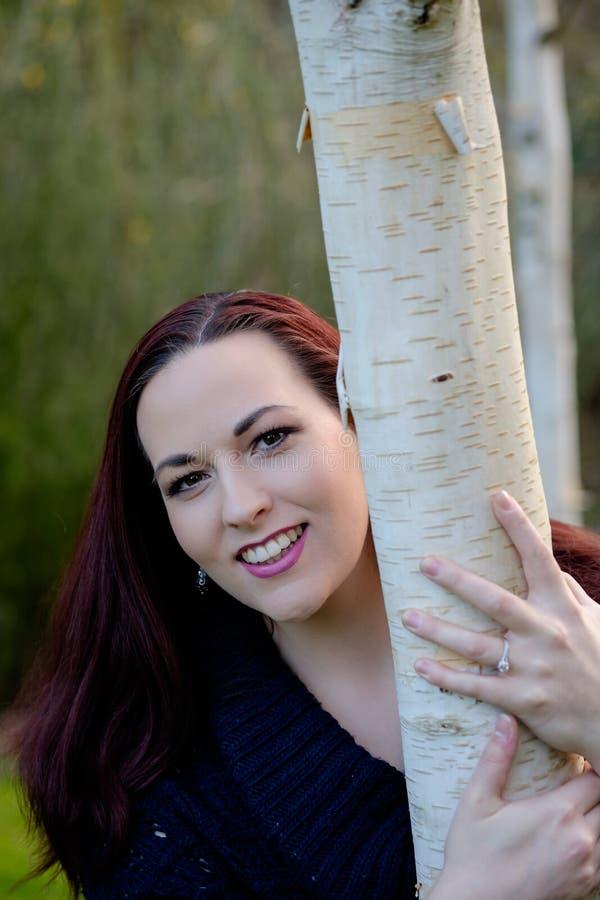 Retrato das jovens mulheres que guardam a árvore imagens de stock royalty free