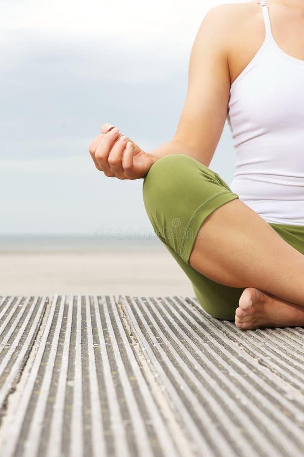Retrato das mãos fêmeas da ioga na praia imagens de stock