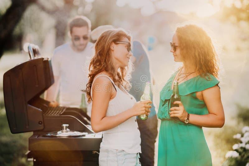 Retrato das meninas felizes que apreciam cervejas claras e que têm uma boa estadia no partido da grade do assado foto de stock royalty free