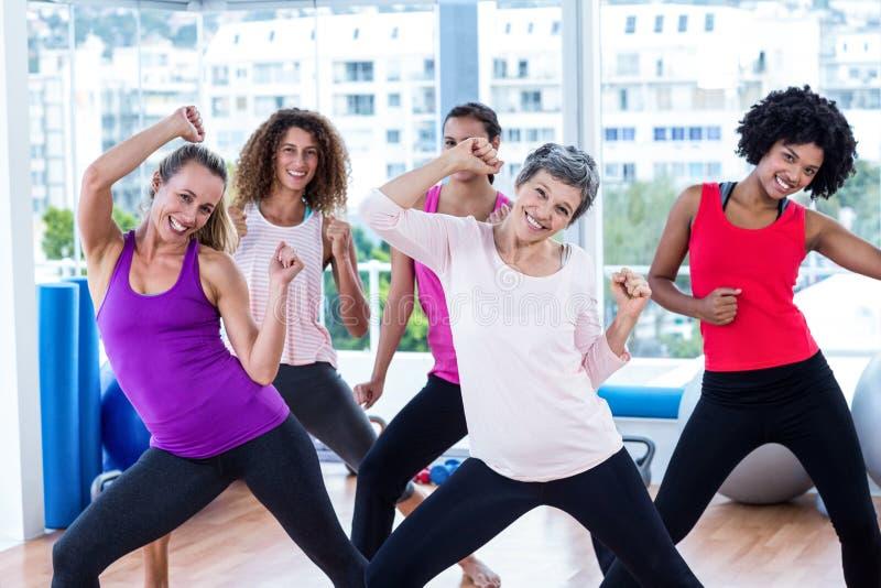 Retrato das mulheres alegres que exercitam com mãos abraçadas imagens de stock