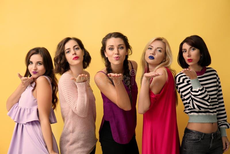 Retrato das mulheres bonitas que fundem beijos no fundo da cor fotos de stock