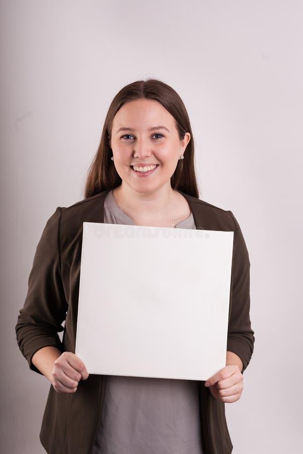 Retrato das mulheres profissionais que guardam um sinal vazio foto de stock royalty free