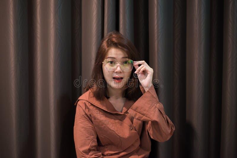 Retrato de óculos de sol tocantes da mulher asiática nova no fundo da cortina imagens de stock