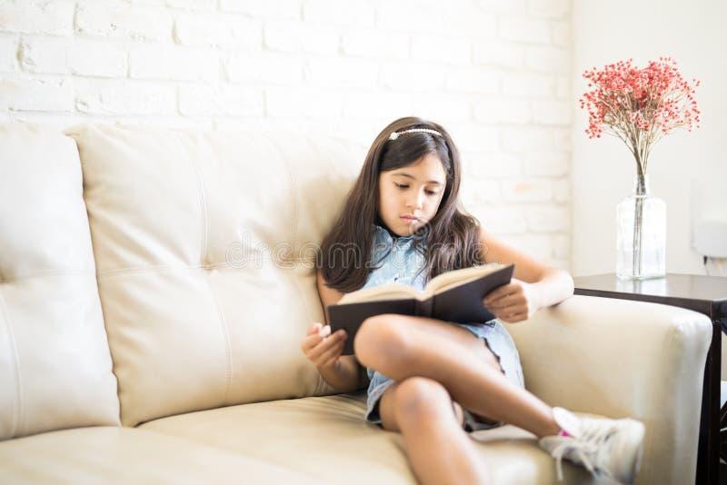 Retrato de 9 años de la muchacha que lee un libro que se sienta en el sofá en foto de archivo
