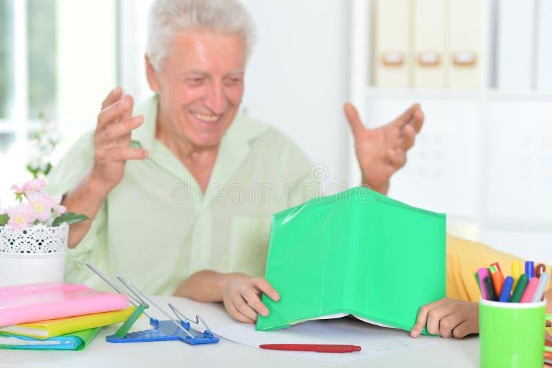 Retrato de abuelo con su nieto haciendo deberes en casa fotos de archivo libres de regalías