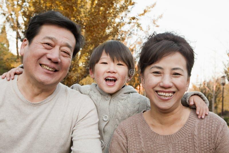 Retrato de abuelos y del nieto felices en el parque en otoño imagenes de archivo