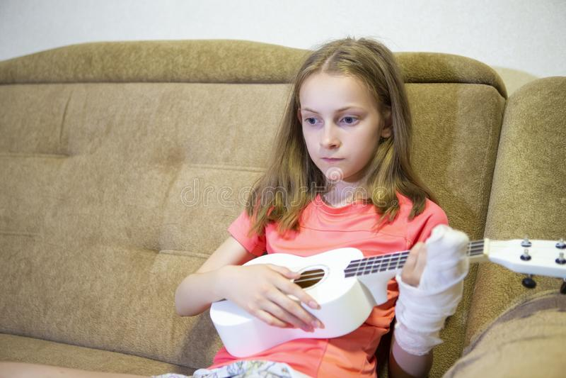 Retrato de afligirse a la muchacha caucásica con la mano herida en el yeso que toca la guitarra hawaiana dentro imagen de archivo libre de regalías