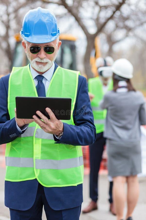 Retrato de alto nivel de empresario o ingeniero de pelo gris que trabaja en una tableta mientras visita el lugar de construcción imágenes de archivo libres de regalías