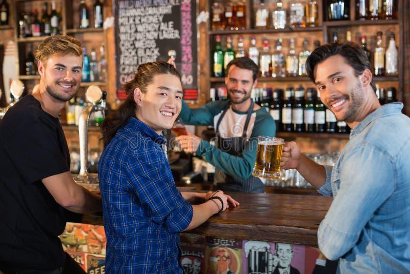 Retrato de amigos de sorriso com barman fotos de stock royalty free