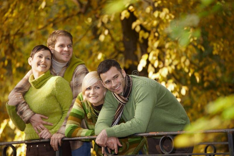 Retrato de amigos jovenes en parque del otoño imagenes de archivo