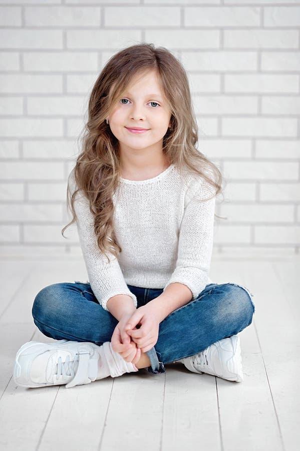 retrato de 7 anos pequenos bonitos da menina idosa que sorri e que senta-se no assoalho de madeira branco no estúdio fotografia de stock