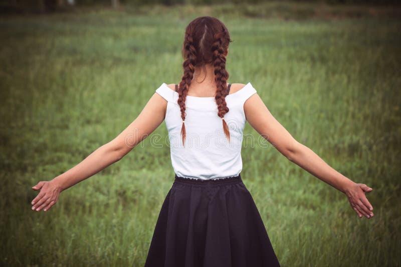 Retrato de apreciar a mulher que levanta suas mãos no campo fotografia de stock